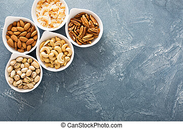 Variety of nuts in small bowls - Variety of nuts in small...