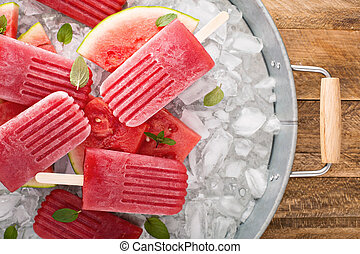 Watermelon and strawberry popsicles on ice filled tray