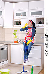 Cleaning lady restng on kitchen countertop - Tired young...