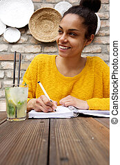 Young woman sitting at cafe and writing notes - Portrait of...