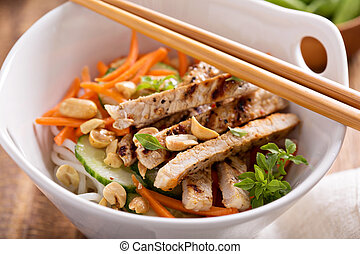 Asian cuisine chicken salad with rice noodles, carrot and...