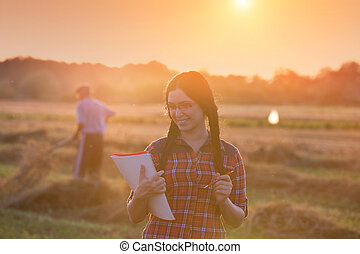 Farmer girl in field at sunset - Young farmer girl writing...