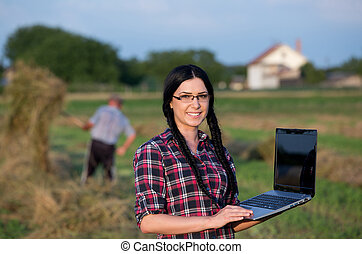Farmer girl with laptop on ranch - Young pretty girl with...