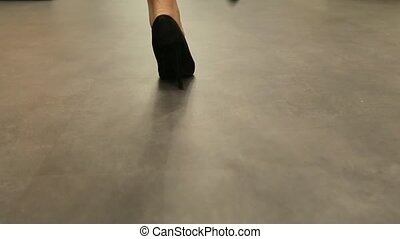Girl walking in black shoes down view