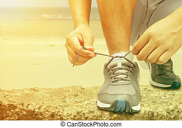 young man runner tying shoelaces