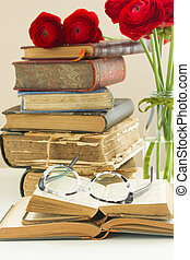 Old books with rose flower - Stack of old vintage books with...
