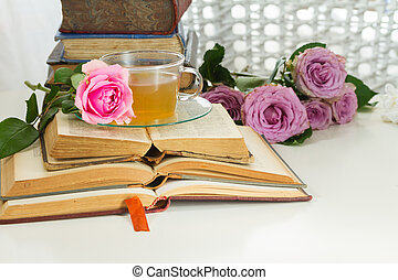 Old books with rose flower - Pile of vintage books with...