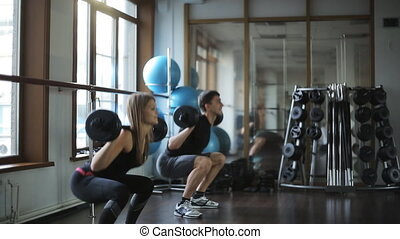 Man and woman doing squats with a barbell behind your head....