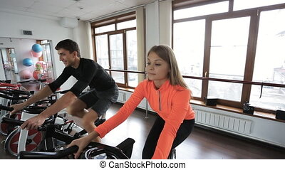 Couple on a stationary bike at gym with big windows. This...