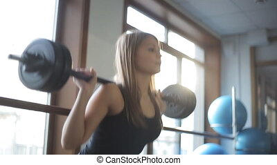 A woman squats with a barbell behind head in front of large...