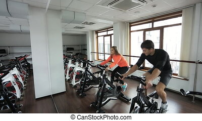 Two Athlete engaged on a stationary bike in gym.This...