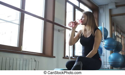 Young woman has rest drinking water in gym. She knows a lot...