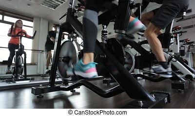 Woman and man do on exercise bike in room with a glass wall.