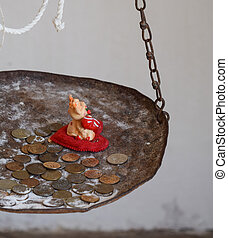 Figurine of a cow on a heart in the scales with coins Coins...
