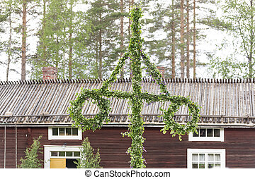 Swedish Traditional Midsummer Pole (Maypole) with a building...