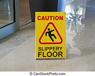 Caution slippery floor - Sign saying caution in english with...