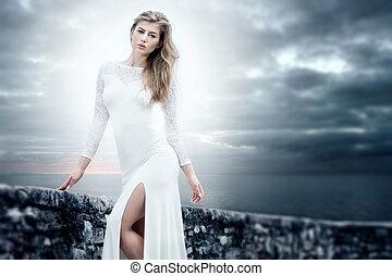 Elegant girl in white dress posing.