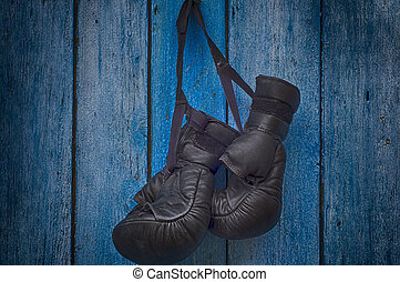 pair of black gloves for Thai boxing hanging on a nail in...