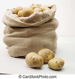 overflowing bag of potatos on whit - smale bag of potoatos