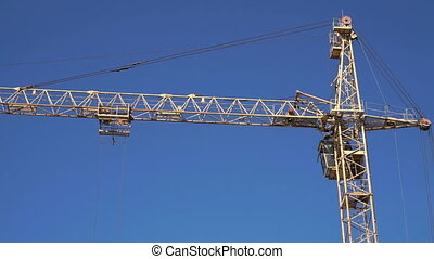 One construction crane working in the blue sky