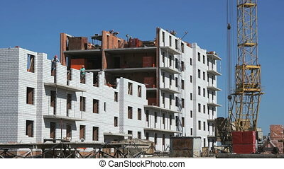 Builders put the brickwork on a construction site - The...