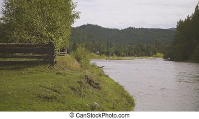 Wooden fence is on one side of large river, trees and...