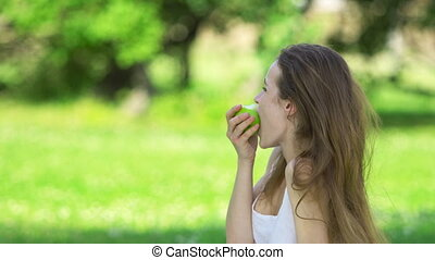 Young woman biting and eating tasty green apple in a city...