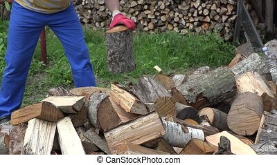 close up of worker man chop wood with axe in country yard....