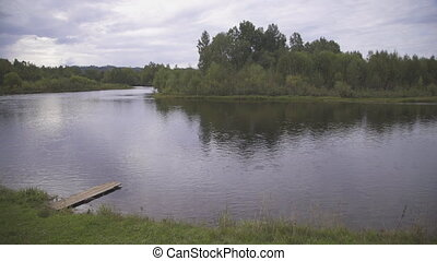 Calm wide river with wooden platform is surrounded by forest...