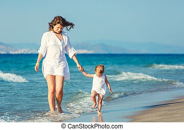 Mother and daughter walking on the beach - Mother and little...