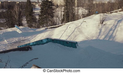 Extreme snowboarder slide on the rails in the park