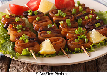 Squid rings on skewers with lemon macro horizontal - Squid...