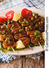 Squid rings on skewers with lemon macro. Vertical - Squid...