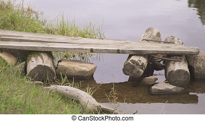 Homemade wooden bridge from logs and stones built in calm river.