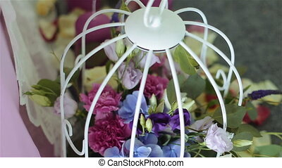 Wedding table decorated with birds cage, flowers, and pearl...