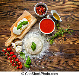 Pizza dough with tomato sauce on wooden table - Pizza dough...