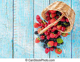 Berry fruit in basket placed on old wooden planks - Fresh...
