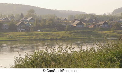 Russian wood village situated on banks of river in morning...