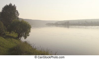 Wide smooth deep river flows slowly in large valley in morning mist.