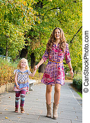 Full length portrait of mother and daughter walking at the...