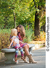 Happy mother and daughter sitting on the bench at the park....