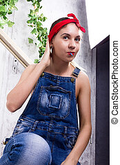 beautiful young woman in denim overalls and a bandana looking at the camera as the mirror, Chupa Chups licking and posing