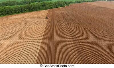 Farmer seeding, sowing crops at field.Aerial view. - Aerial...