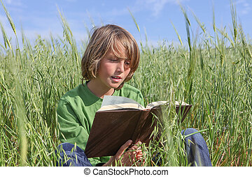 child reading book or bible outdoors.