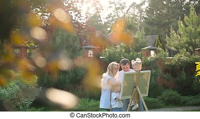 Young family painting on an easel in the garden