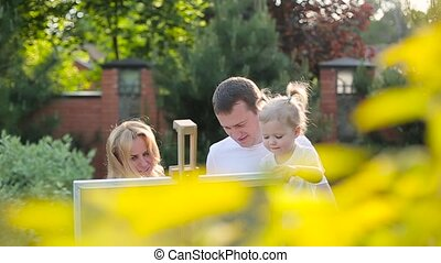 Young family painting on an easel in the garden.