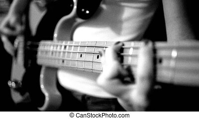 playing the electric bass guitar black and white