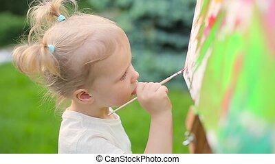 Little girl draws on an easel