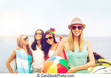 girl with ball and friends on the beach - summer holidays,...