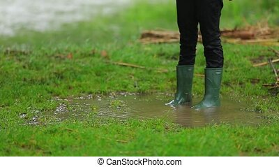 Child In Rubber Boots Standing In Puddle - SLOW MOTION....